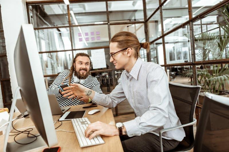Trevlig smart man som ler till hans kollega arkivfoton
