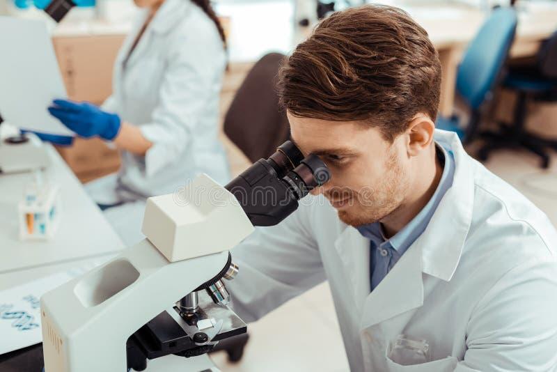 Trevlig stilig biolog som använder ett yrkesmässigt mikroskop arkivfoto