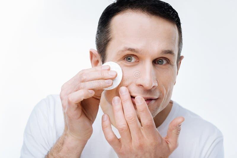 Trevlig stilig man som att bry sig om hans hud fotografering för bildbyråer