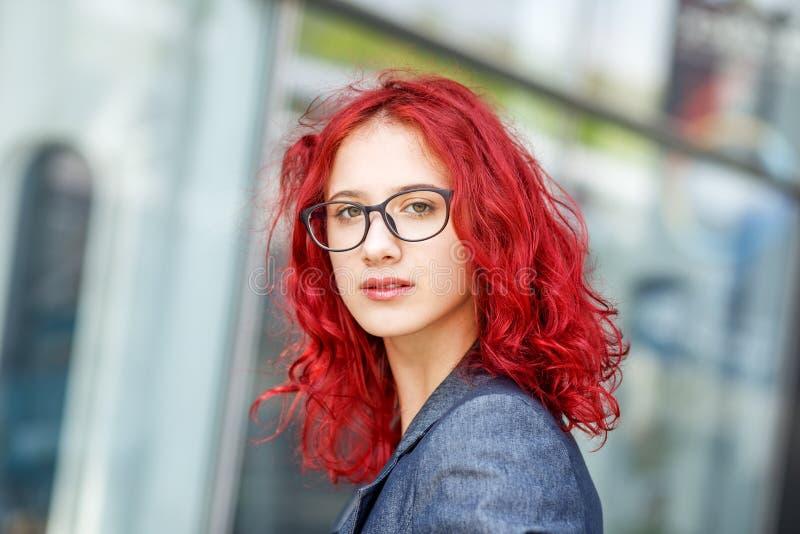 Trevlig ung flicka med exponeringsglas och rött hår Begrepp av livsstilen, stående, utbildning arkivbild