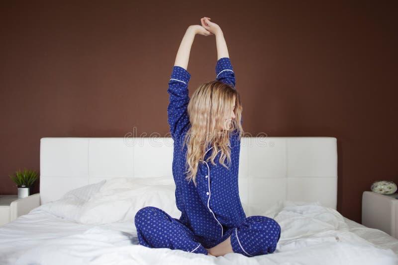 Trevlig ung kvinna, gladlynt morgon, elasticiteter som sitter på sängen royaltyfri fotografi
