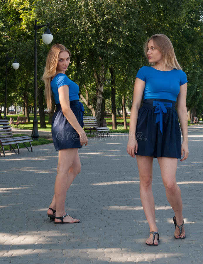 Trevlig ung kvinna i blå kort kjol med hennes tvilling- royaltyfri foto