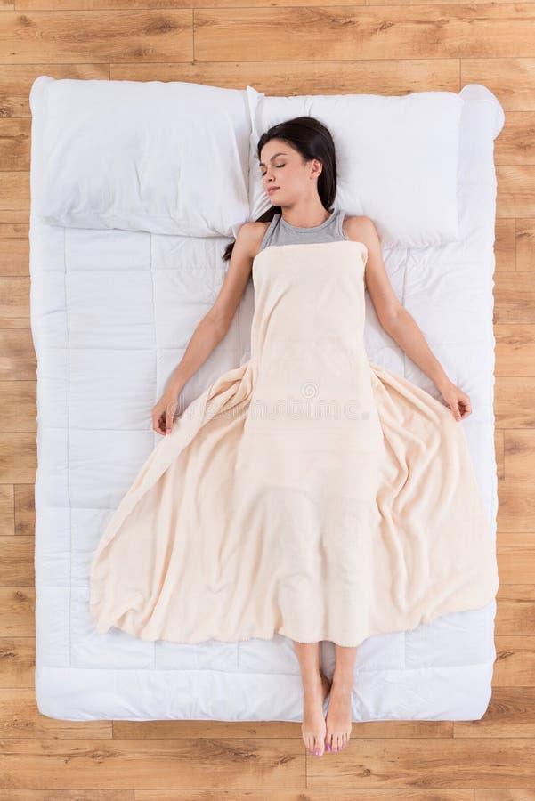 Trevlig ung kvinna som ligger och sover på säng arkivfoton