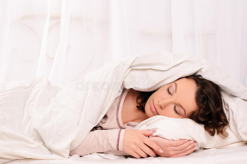 Trevlig ung kvinna som sover på vit säng royaltyfri fotografi