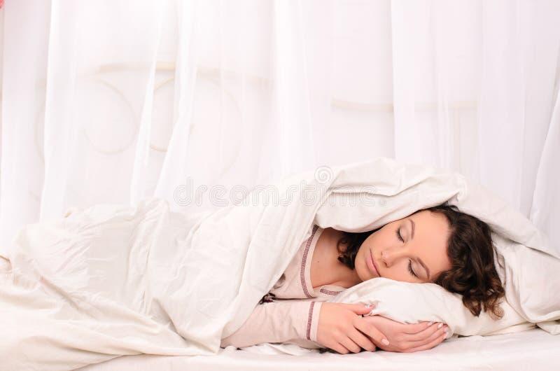 Trevlig ung kvinna som sover på vit säng arkivfoton