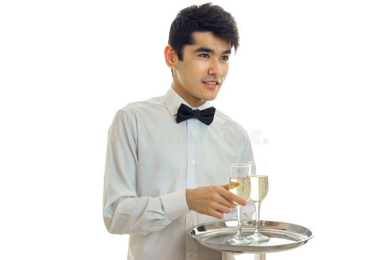 Trevlig ung uppassare i en skjorta som rymmer ett magasin med exponeringsglas av champagnenärbild royaltyfria foton