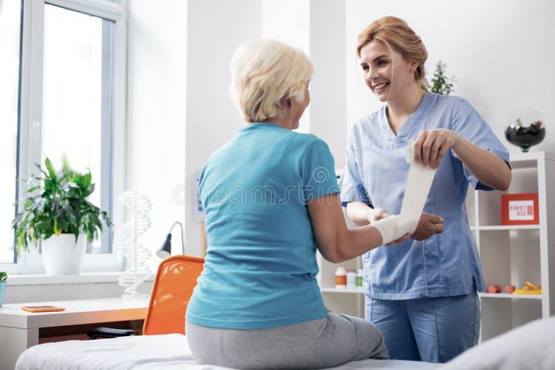Trevlig vänlig kvinnlig sjuksköterska som gör hennes jobb arkivbild