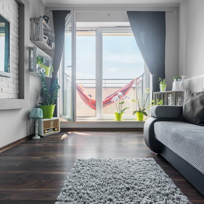 Trevlig vardagsrum med stora fönster fotografering för bildbyråer