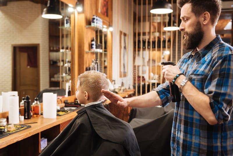 Trevlig yrkesmässig barberare som besprutar vatten på hans hand arkivfoto