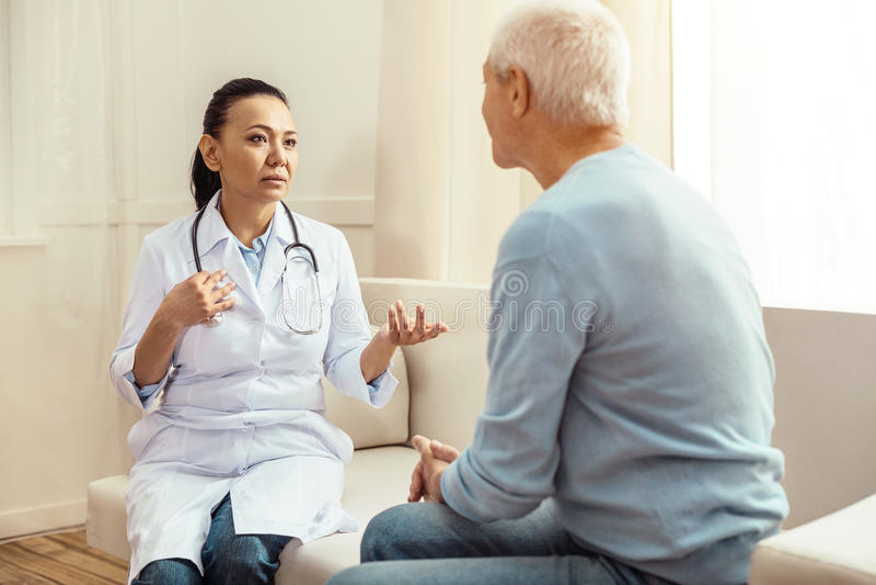 Trevlig yrkesmässig doktor som ser hennes patient arkivfoto