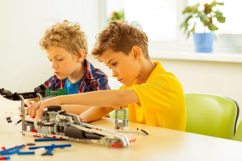 Trevliga allvarliga pojkar som fokuseras på deras arbete royaltyfri bild