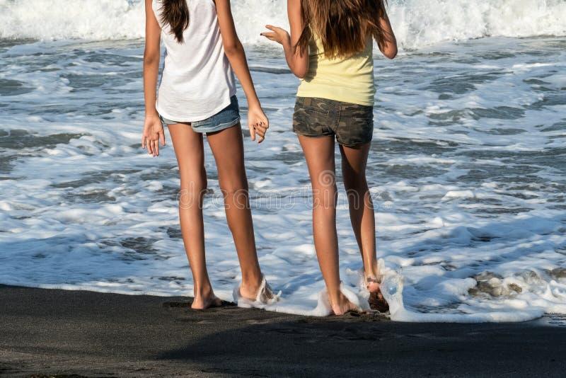 Trevliga ben av en nätt flicka i jeans kortsluter anseende i vatten Närbildsikten av flicka` s lägger benen på ryggen på stranden arkivfoton
