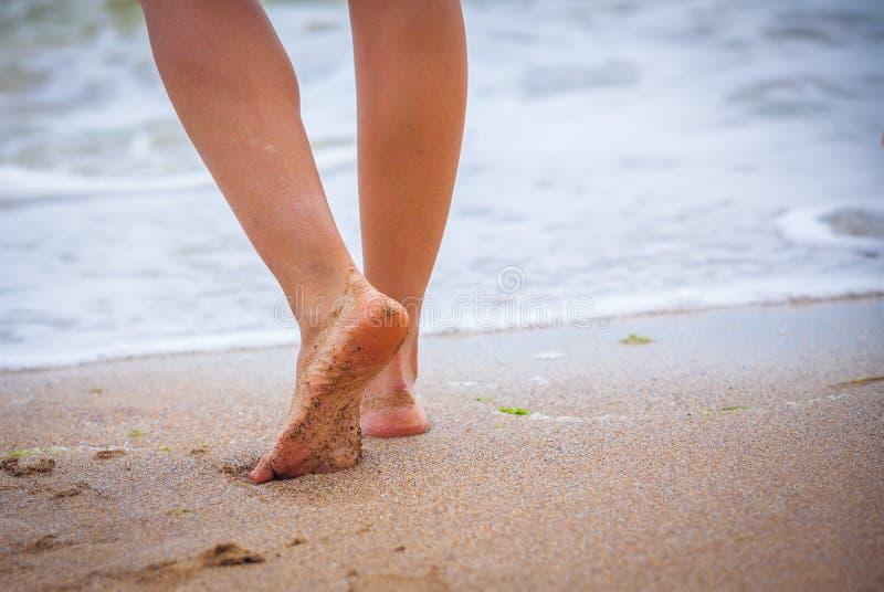 Trevliga ben av en nätt flicka som går i vatten arkivbild
