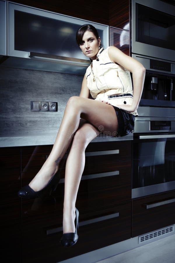 Trevliga brunete i kök fotografering för bildbyråer