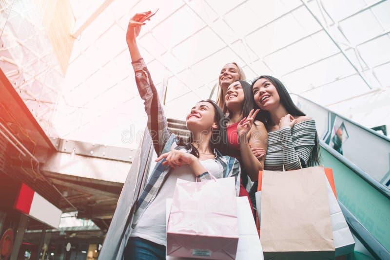 Trevliga flickor tar selfie på rulltrappan i galleria De rymmer många påsar, därför att de shoppar fotografering för bildbyråer