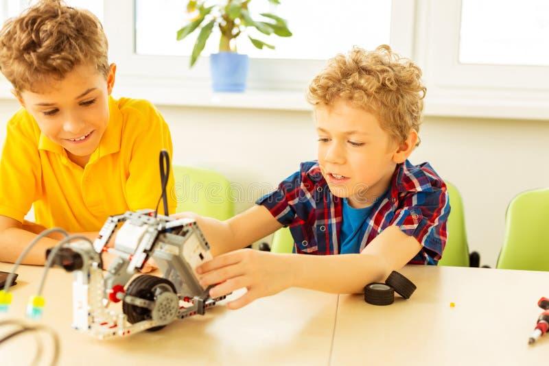 Trevliga intresserade pojkar som arbetar på vetenskapsprojektet royaltyfri foto