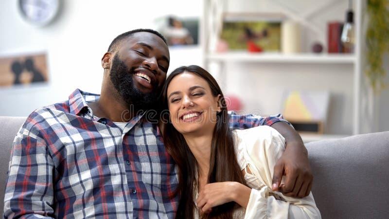 Trevliga multietniska par som hemma ler och sitter på soffan och att ha gyckel tillsammans royaltyfri foto