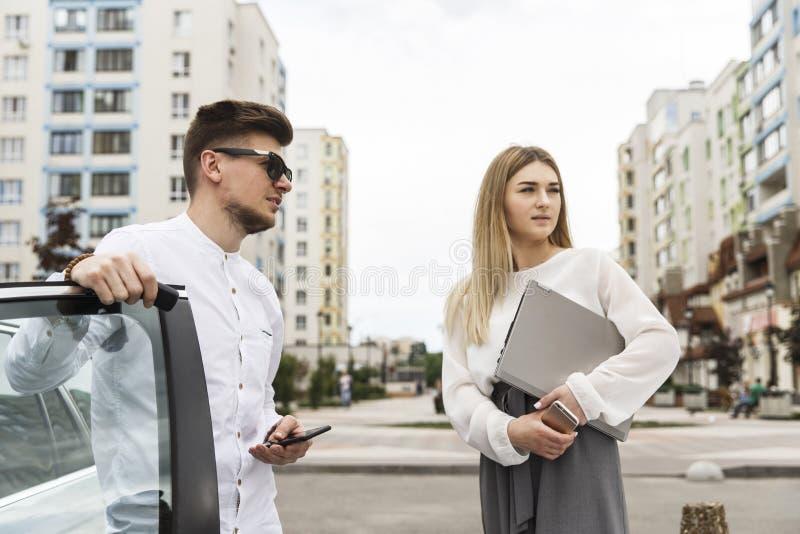 Trevliga par står tillsammans utvändiga på gatan Grabben lutar på bilens dörr Han b?r exponeringsglas Flickan ser samma fotografering för bildbyråer