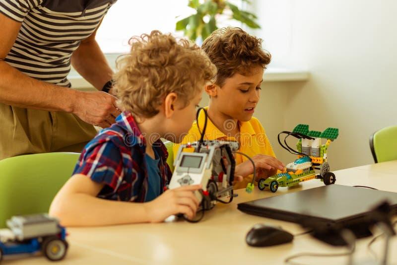 Trevliga smarta pojkar som ser bilmodellerna fotografering för bildbyråer