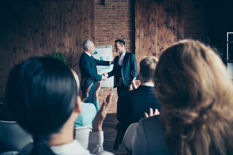 Trevliga stilfulla yrkesmässiga gladlynta bästa chefer som bär mörka dräkter som skakar händer, välkomnar till ny startfinans för fotografering för bildbyråer