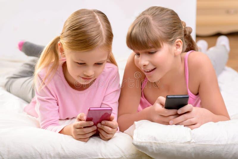 Trevliga systrar som ligger på soffa royaltyfria bilder