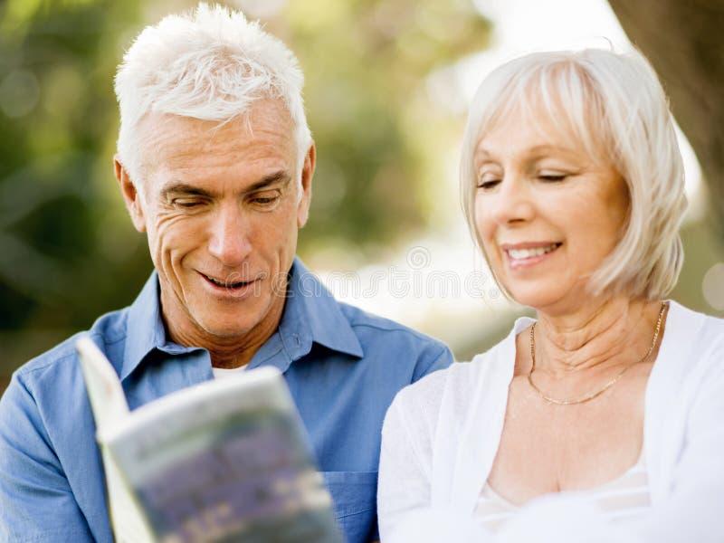 Download Trevligt åldringparsammanträde Utomhus Med Boken Arkivfoto - Bild av pensionerat, avkoppling: 78730760