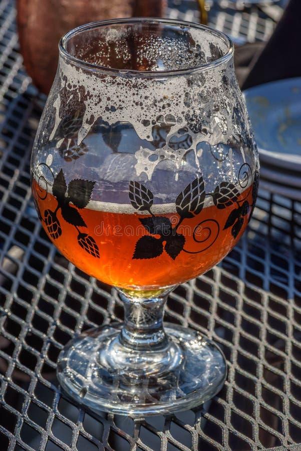 Trevligt bärnstensfärgat exponeringsglas av öl på den utomhus- uteplatstabellen arkivbilder