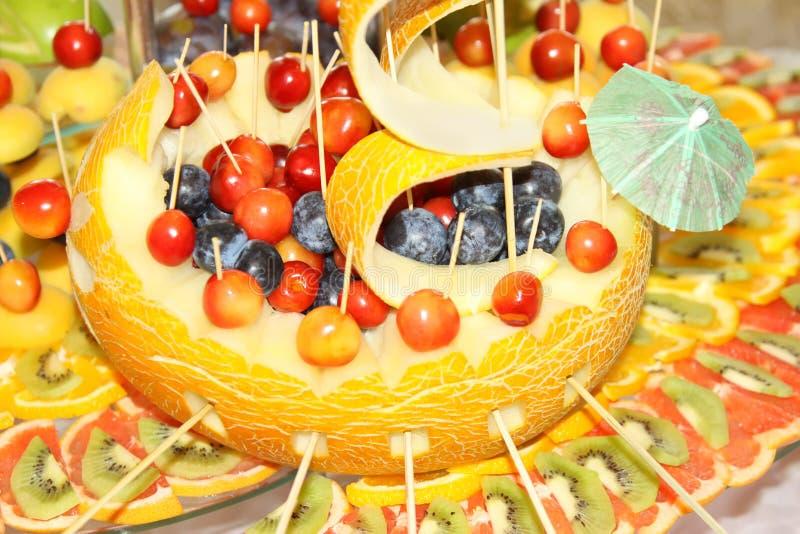 Trevligt dekorativt fartyg med melon, körsbäret, grapefrukten och druvan royaltyfri bild