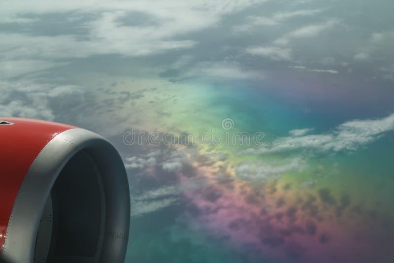 Trevligt fragment av en sikt från på flygplanklättring ovanför härliga färgmoln för regnbåge som kommer med uppmärksamhet royaltyfri bild