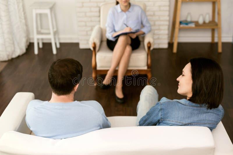 Trevligt gift par som sitter mitt emot deras terapeut royaltyfria bilder