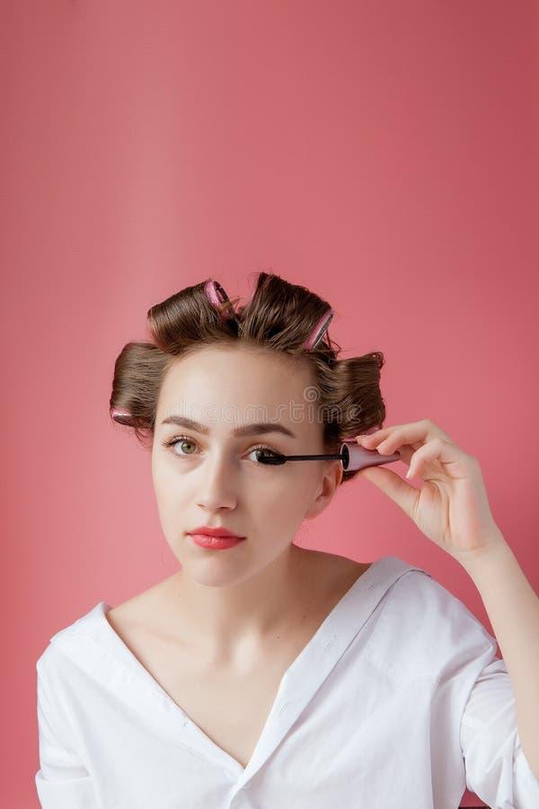 Trevligt gladlynt ungt flickan i hårrullen målar ett ögonbryn på rosa bakgrund royaltyfri bild