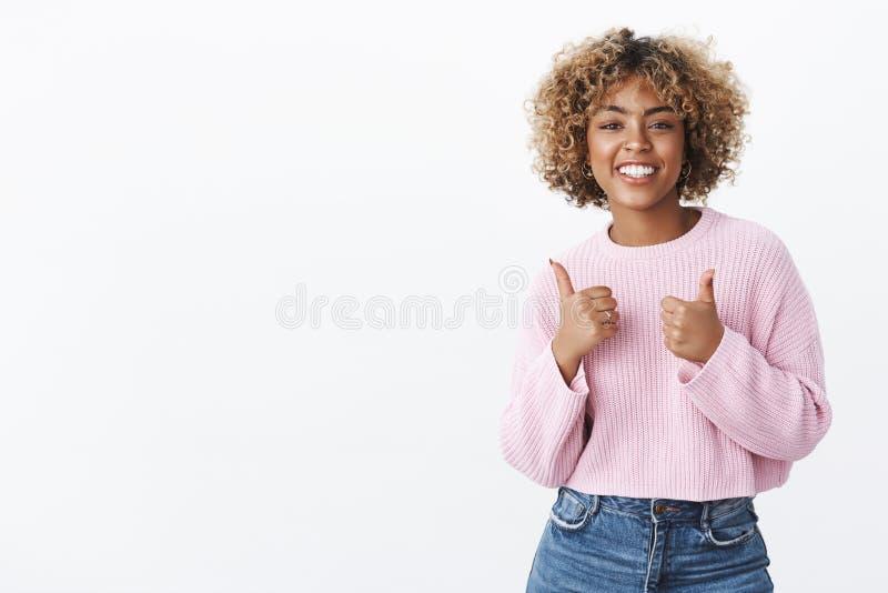 Trevligt jobb, kallt resultat St?ende av denseende f?rtjusta attraktiva glade afrikansk amerikankvinnan med blont lockigt royaltyfri bild
