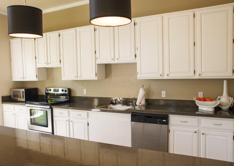 Trevligt kök med vita skåp arkivbilder