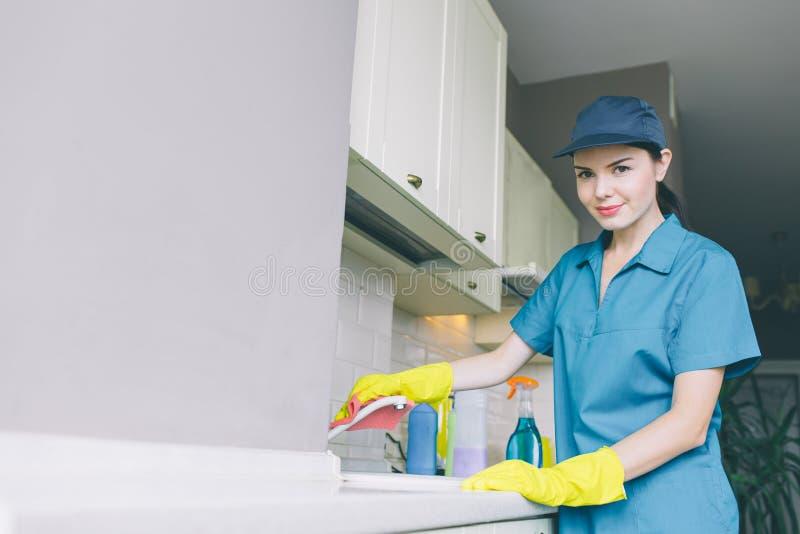 Trevligt och attraktivt rengöringsmedel i rör för locklokalvårdvatten och blick på kamera Hon bär blåa enhetliga och gula handska royaltyfri fotografi