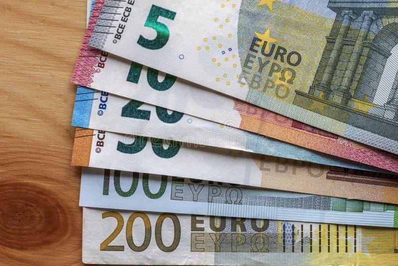 Trevligt ordnad bunt av eurosedlar, värde för valutaräkningar tio, euro tjugo, ett och tvåhundra och olika metallmynt royaltyfri foto
