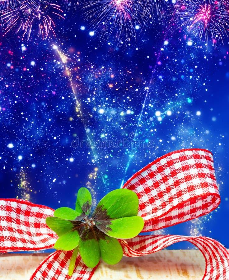 Trevo afortunado na frente do céu da véspera de Ano Novo com fogos de artifício fotografia de stock royalty free