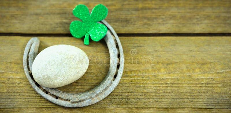 Trevos do dia do St Patricks com ferradura e seixo fotos de stock royalty free