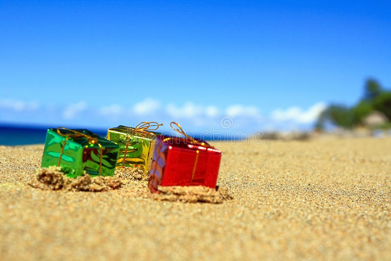 Trhee colour gift boxes on beach of ocean stock images