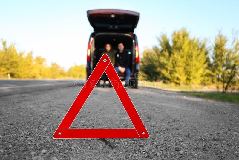 Triángulo amonestador rojo en la carretera de asfalto imagenes de archivo