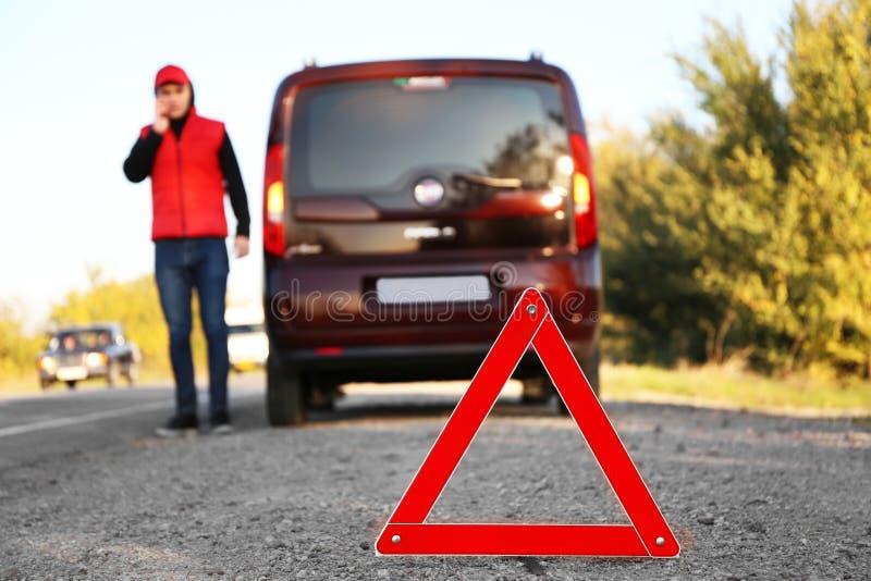 Triângulo de advertência vermelho na estrada asfaltada imagem de stock