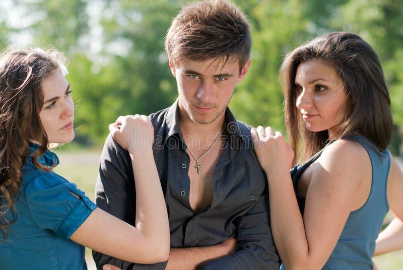 Triângulo de amor: mulheres de um homem dois que levantam ao ar livre foto de stock