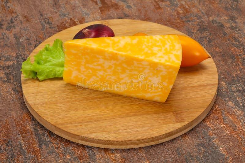 Triângulo de mármore do queijo sobre de madeira foto de stock