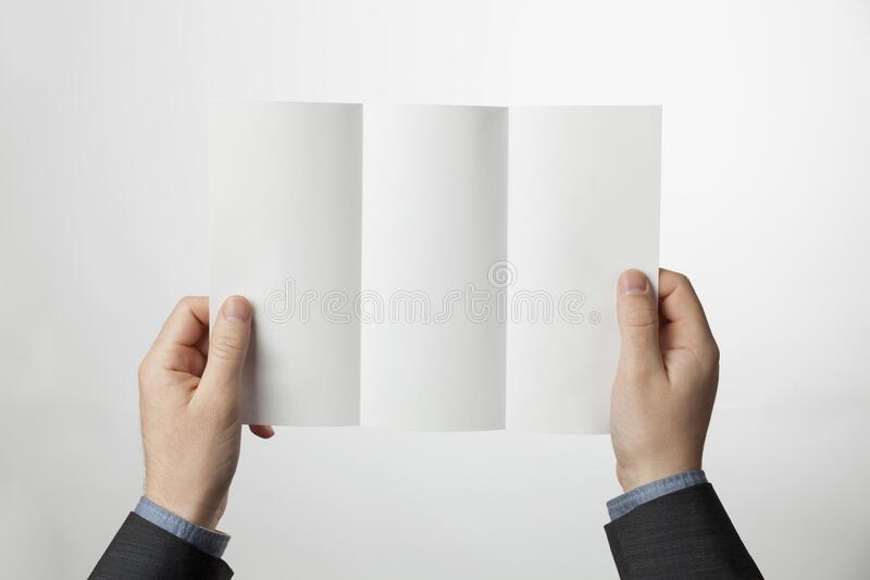 Tri-fold paper brochure in hands. Z-fold design blank for marketing or advertising royalty free stock photo