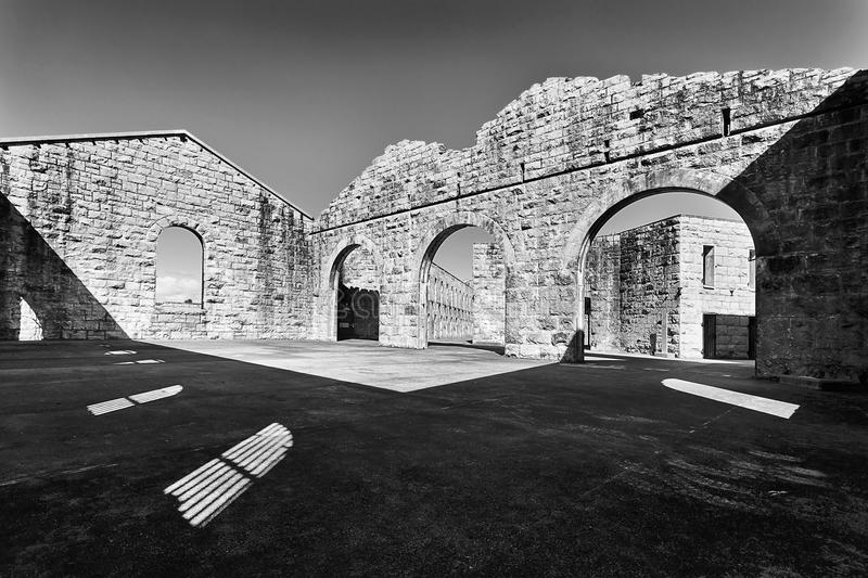 Trial bay gaol BW. Inner yard of stone with brick walls but no roof in historic heritage Trial Bay Gaol of NSW of Australia. Contrast black-white impression of royalty free stock photo