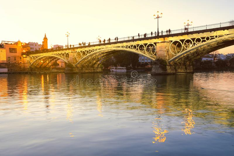 Triana bridge over Guadalquivir river. Isabel II bridge or Triana bridge over Guadalquivir river with it`s reflection at twilight, Seville, Andalusia, Spain stock photos