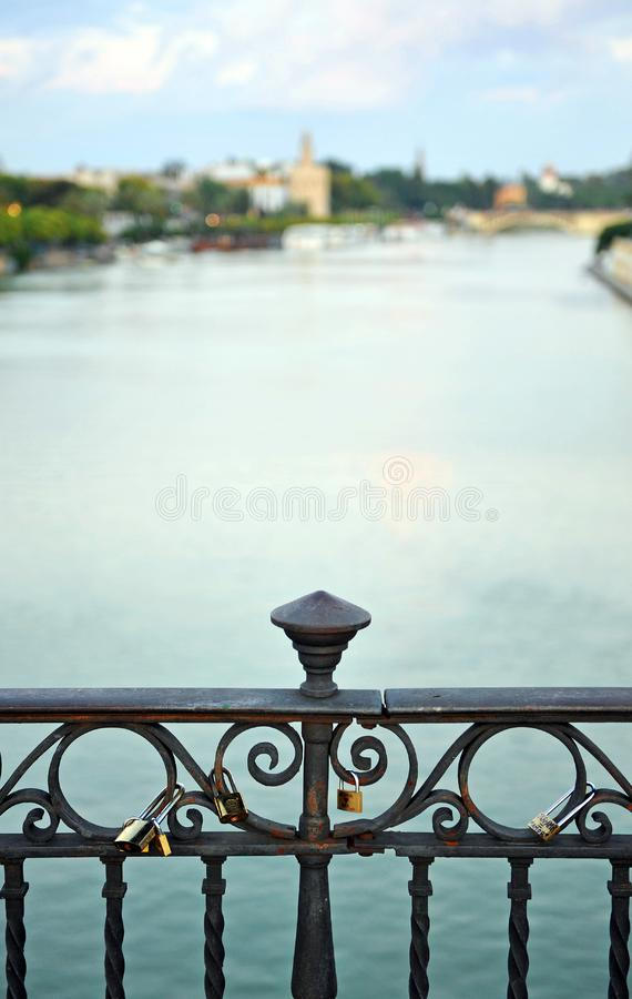 Triana bridge over the Guadalquivir River, Seville, Andalusia, Spain. Padlocks in one of the bridges that connect the two banks of the Guadalquivir river as it stock photography