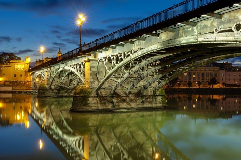 Triana bro Sevilla på skymning royaltyfria bilder