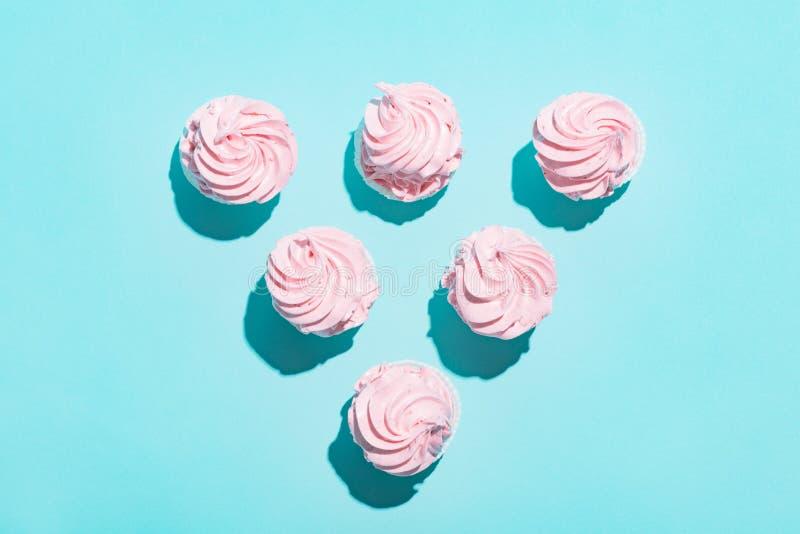 Triangel av rosa muffin på blå bakgrund royaltyfria foton