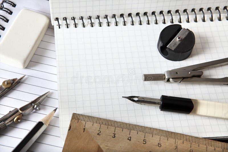 Triangellinjalen, passaren, avdelare, radergummit, en enkel blyertspenna och en vässare ligger på en anteckningsbok ovanför sikt  royaltyfri fotografi