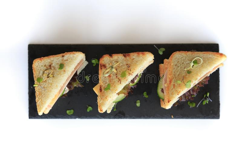 Triangle club sandwich tripple set on black ceramic plate against white background. Triangle club sandwich tripple set on black ceramic plate part of series stock photos
